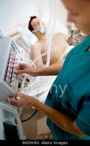 intensive-care-patient-nurse-adjusting-controls-on-a-ventilator-attached-B6DW8G